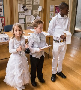 Children ready for first communion, carrying offering for eucharist